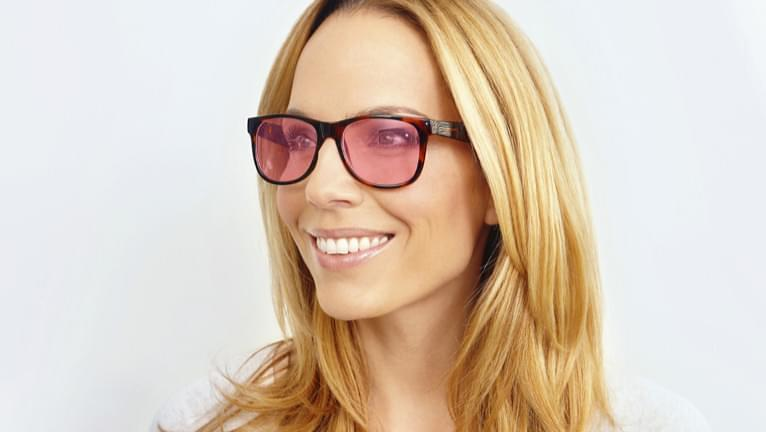 Pink tinted sunglasses are stylish when paired with blonde hair.