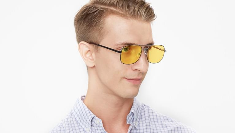 Yellow tinted sunglasses are stylish when paired with brown hair.