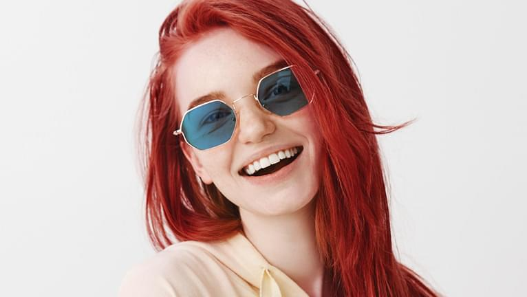 Blue tinted sunglasses are stylish when paired with red hair.